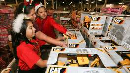 Rebecca Hernandez (from left), 10, Katelyn Montanez, 11, and Serena Leal, 10, from Kate Schenck Elementary pick out presents for a 6-year-old boy and a one-year-old girl as volunteers gathered to wrap presents for the Elf Louise Christmas Project at Port San Antonio Dec. 3, 2014.