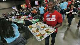An H-E-B employee carries a plate of food for guests arriving at the 2015 H-E-B Feast of Sharing at the Convention Center . Thousands of people annually gather for the pre-Christmas event to share a meal and to take in the festivities hosted by the local grocery chain.