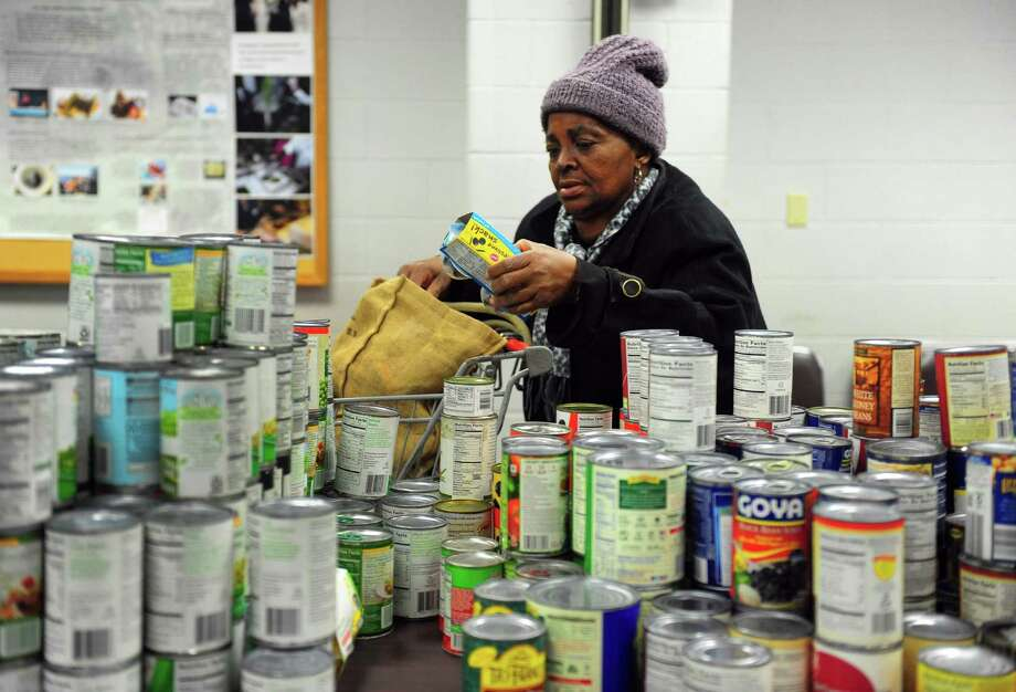 Dalvis Lynch fills her bag with holiday food during the 7th Annual Feed the People Food Pantry Thanksgiving Food Drive held at the Aquaculture School in Bridgeport, Conn. on Tuesday Nov. 22, 2015. The drive was held at the Aquaculture School for the first time so some of the students could volunteer and because the school donated some of the food. The Feed the People Food Pantry is located at the P.T. Barnum Apartments and accommodates food for over 500 families. Its founder, Prophetess Geraldine Claytor, passed away in 2015 and her daughter Bennyta Thompson took over organizing the event. Photo: Christian Abraham / Hearst Connecticut Media / Connecticut Post