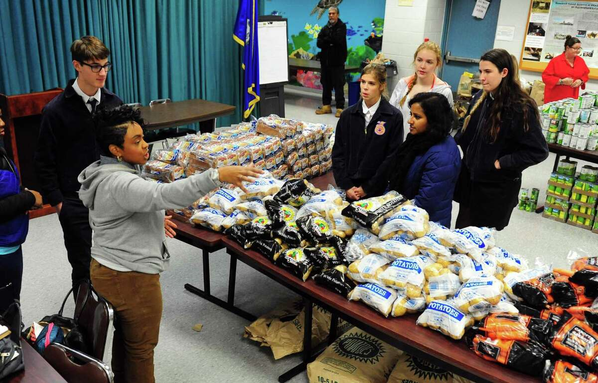 Bennyta Thompson, with the Feed the People Food Pantry, at left, directs volunteers during the 7th Annual Feed the People Food Pantry Thanksgiving Food Drive held at the Aquaculture School in Bridgeport, Conn. on Tuesday Nov. 22, 2015. The drive was held at the Aquaculture School for the first time so some of the students could volunteer and because the school donated some of the food. The Feed the People Food Pantry is located at the P.T. Barnum Apartments and accommodates food for over 500 families. Its founder, Prophetess Geraldine Claytor, passed away in 2015 and her daughter Bennyta Thompson took over organizing the event.