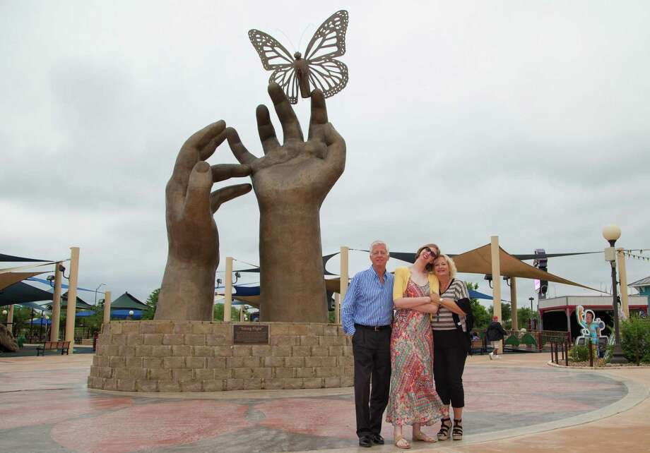 Morgan's Wonderland founder Gordon Hartman, daughter Morgan and wife/mother Maggie Hartman pose by the large sculpture of hands and a butterfly just inside the theme park for people with special needs. More more information on the park in San Antonio, go to morganswonderland.com. Photo: Courtesy Photo