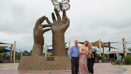 Morgan's Wonderland founder Gordon Hartman, daughter Morgan and wife/mother Maggie Hartman pose by the large sculpture of hands and a butterfly just inside the theme park for people with special needs. More more information on the park in San Antonio, go to morganswonderland.com.