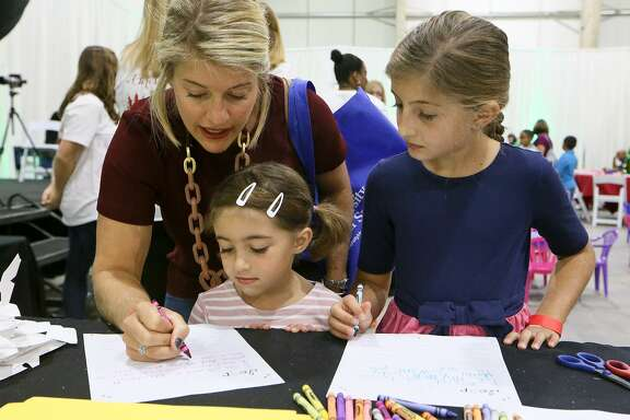 Olivia Malitz helps her daughter, Elise, 4, with a letter to Santa as her other daughter, Olivia, 8, looks on during a Breakfast with Santa at the Holiday Olé Market, a Junior League of San Antonio fundraiser, at Joe Freeman Coliseum in October. Proceeds from the market benefit the community programs and projects of the Junior League, including Goodwill, Boysville, Children's Shelter, Green Space Alliance, Arc of SA and many more.