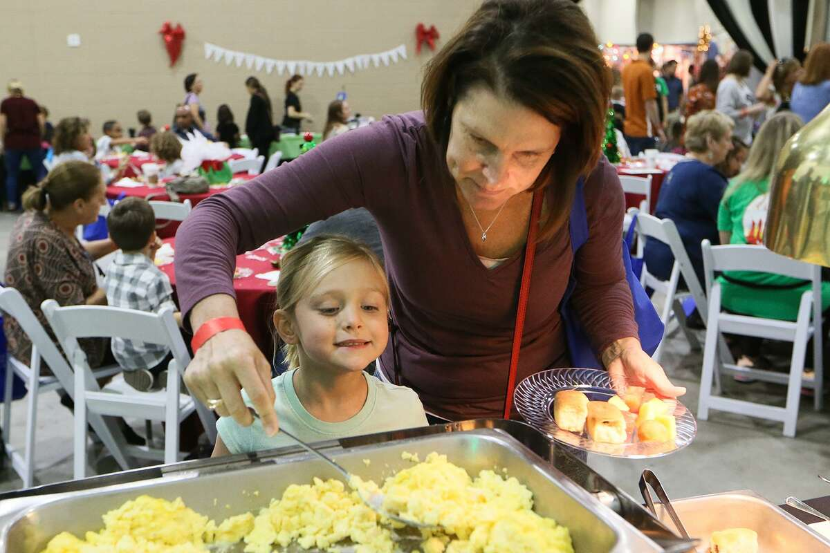 Christine Gard helps her daughter, Sophia Gard, 6, with her plate during a Breakfast with Santa at the Holiday Olé Market, a Junior League of San Antonio fundraiser, at Joe Freeman Coliseum in October. Proceeds from the market benefit the community programs and projects of the Junior League, including Goodwill, Boysville, Children's Shelter, Green Space Alliance, Arc of SA and many more.