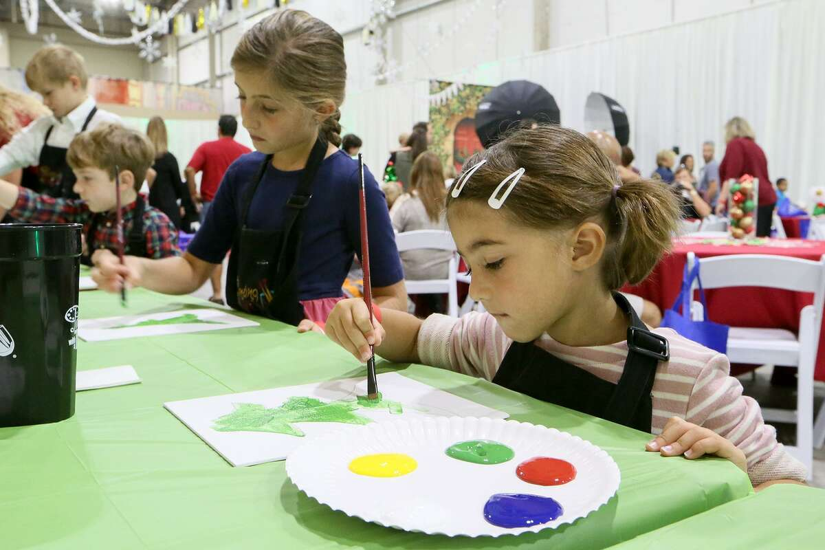 Elise Malitz, 4, (right) and her sister, Olivia Malitz, 8, paint Christmas trees during a Breakfast with Santa at the Holiday Olé Market, a Junior League of San Antonio fundraiser, at Joe Freeman Coliseum in October. Proceeds from the market benefit the community programs and projects of the Junior League, including Goodwill, Boysville, Children's Shelter, Green Space Alliance, Arc of SA and many more.