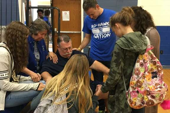 Mike Miller (kneeling, wearing glasses) prays with members of the Fellowship of Christian Athletes at Randolph High School.