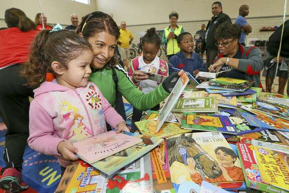 Mary Pacheco (left) helps Jalisa Munoz, 4, pick out a book as cyclists and volunteers with Ride for Reading, delivered books and provided tricycle safety tips to preschoolers at the Carroll Early Childhood Center, 463 Holmgreen Road, in April. Approximately 40 volunteers from USAA and H-E-B participated in the organization's inaugural delivery in San Antonio, taking 650 books to the children.