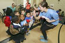 "Devan Hartung (right) ""high fives"" preschoolers at the Carroll Early Childhood Center after they received books from cyclists and volunteers with Ride for Reading on April 1. Approximately 40 volunteers from USAA and H-E-B participated in the organization's inaugural delivery in San Antonio, bringing 650 books to the children."
