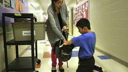 Marizol Cortez, Counselor Clerk at James Madison Elementary School, hands out a bag of food to Richard Perez, 10 years old, a forth grader at the school, on Thursday, Nov. 3, 2016. Perez is a student participant in Snack Pak 4 Kids in San Antonio.