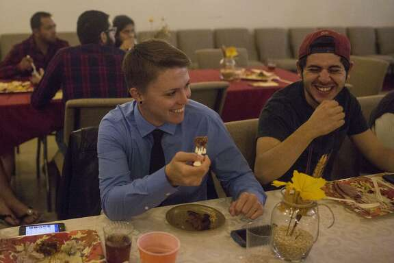 Erin Marquise (left) and Joey Sanchez laugh over dinner during the 10th annual Gay Thanksgiving event at Living Church at Woodlawn Pointe in San Antonio on Nov. 12.