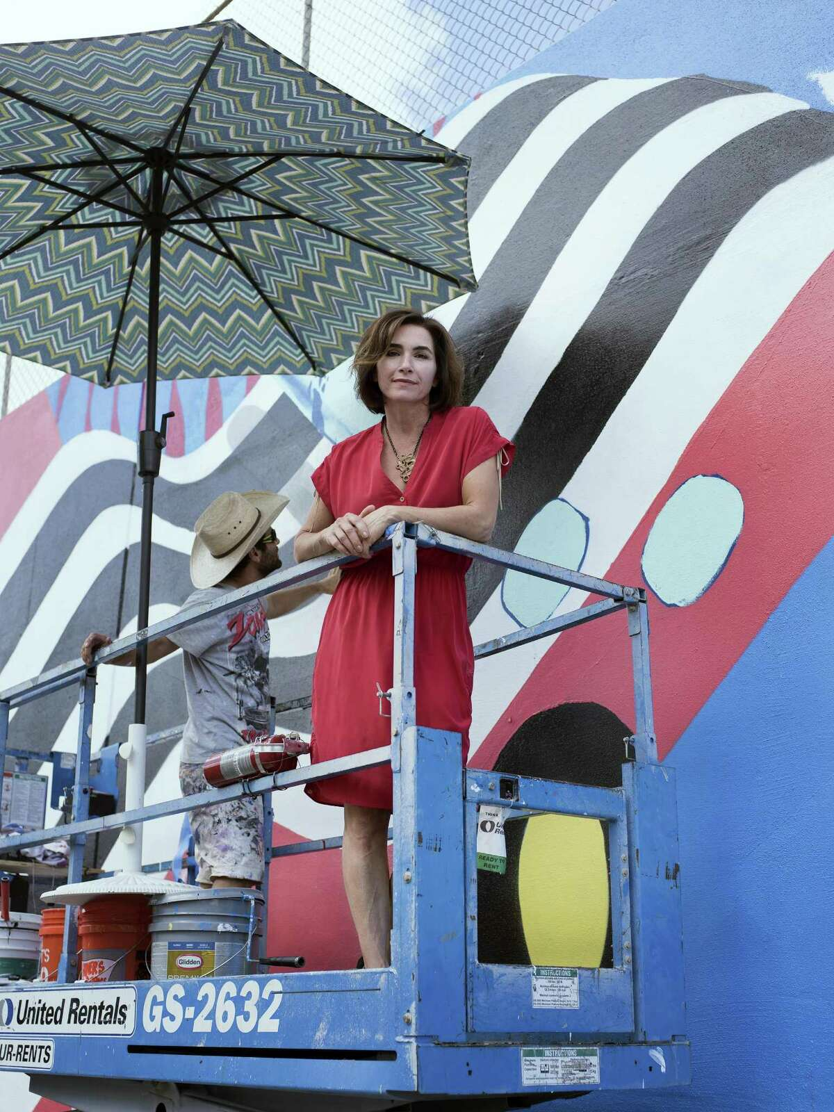 Liz Tullis, president of the board of Luminaria, poses for a portrait by the mural being created by artist Iker Muro (left) in San Antonio on Oct. 28. Tullis has been a member the board of Luminaria since 2010.