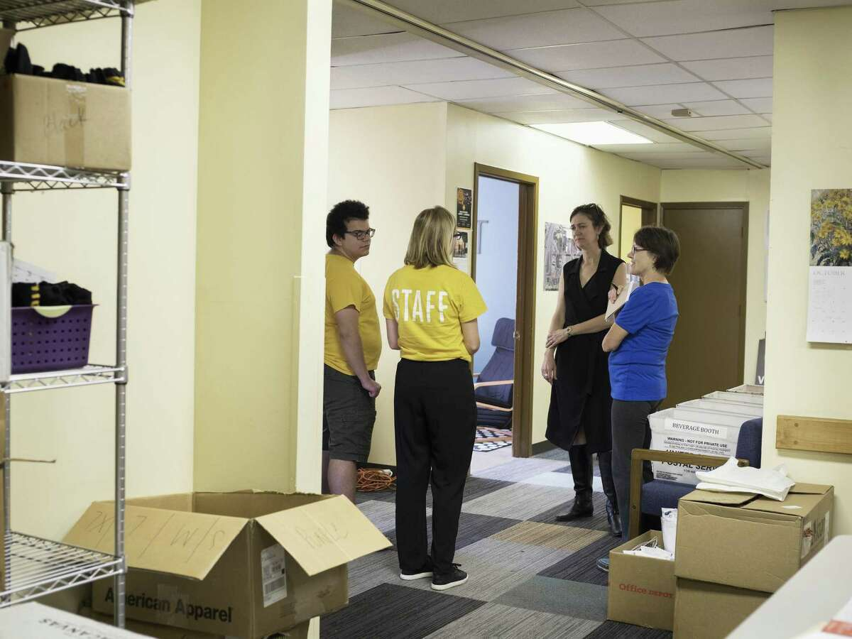 From left, intern Daniel Salas, volunteer coordinator Alyssa Danna, Executive Director Kathy Armstrong and community event organizer Norma Jean Moore talk together as they prepare for Luminaria in their offices in San Antonio on Oct. 28.