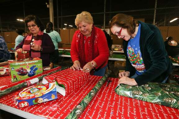 Janie Zamora (from left), Esther Cox and Nelly Sanchez from the Virginia Gill Senior Center wrap presents for a boy and two girls as volunteers gathered to wrap presents for the Elf Louise Christmas Project in Bldg 1470 at Port San Antonio on Dec. 3, 2014. The Elf Louise Christmas Project provides presents for 18,500 children in 5,600 families in the San Antonio Area.