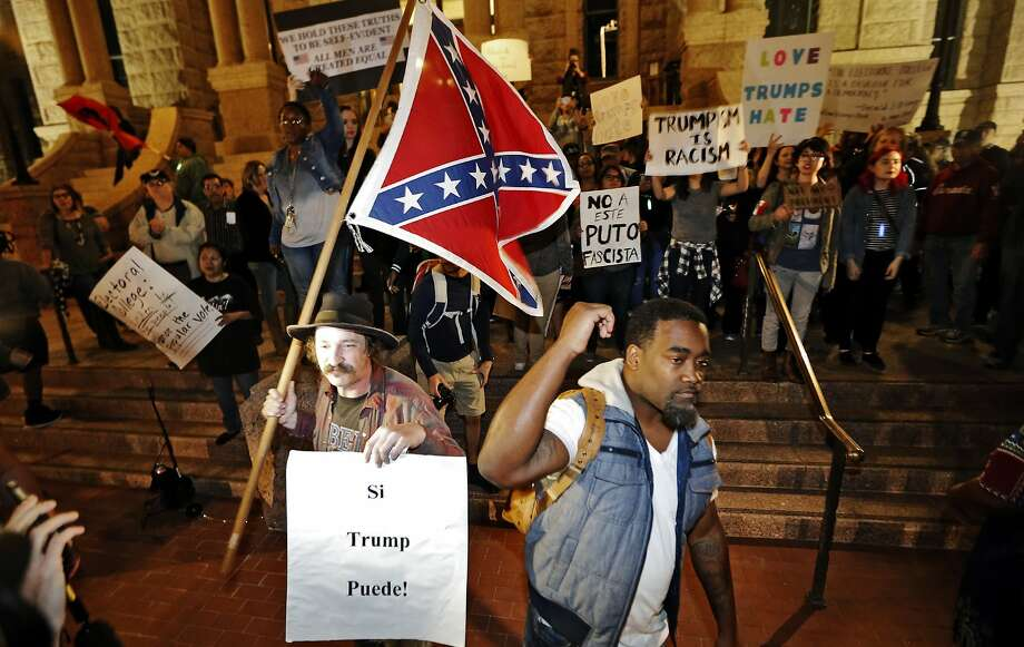 A Trump supporter with a flag, left, counter protests as Mark Hughes, right, President of the Next Generation Action Network, Tarrant County chapter leads a small group outside the courthouse protesting in opposition of President-elect Donald Trump, Friday, Nov., 11, 2016, in Fort Worth, Texas. Photo: Brandon Wade, Associated Press