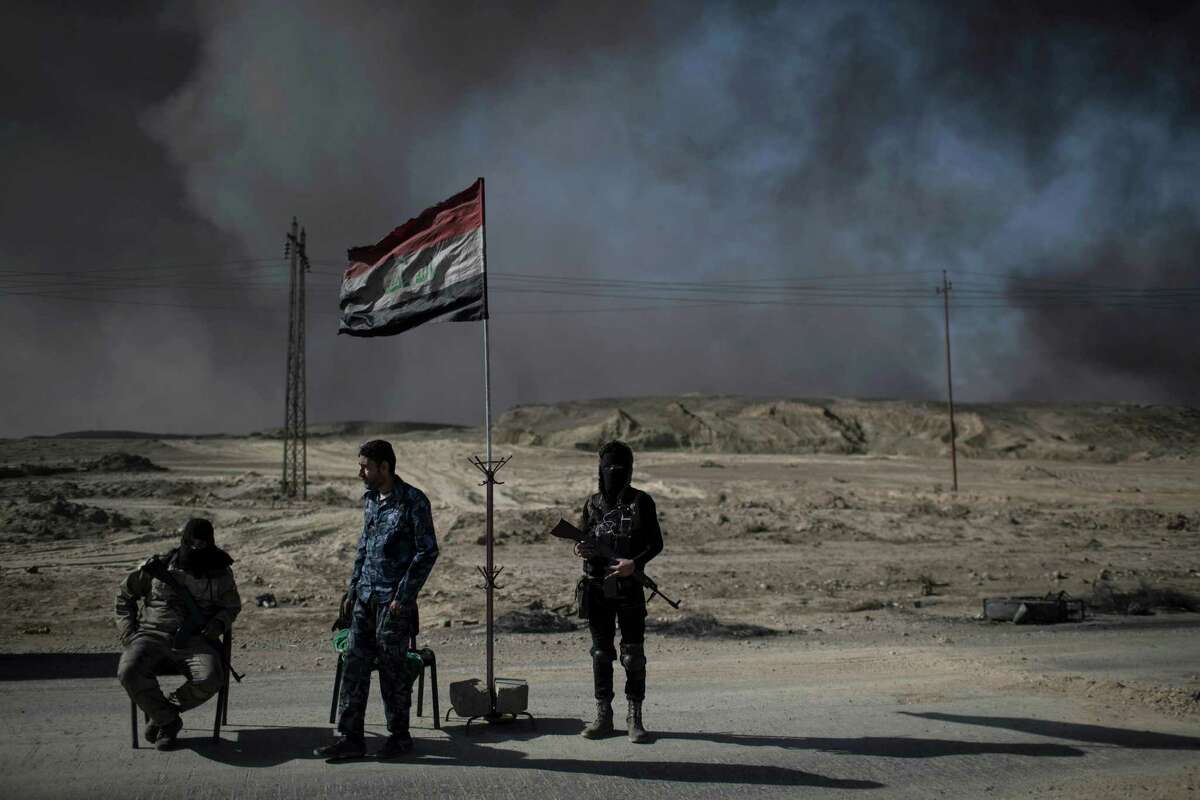 Guards stand at a checkpoint near burning oil fields in Qayara, south of Mosul, Iraq, Tuesday, Nov. 22, 2016. For months, residents of the Iraqi town of Qayara have lived in the darkness from a cloud of toxic fumes released by oil fields lit by retreating Islamic State fighters. (AP Photo/Felipe Dana)