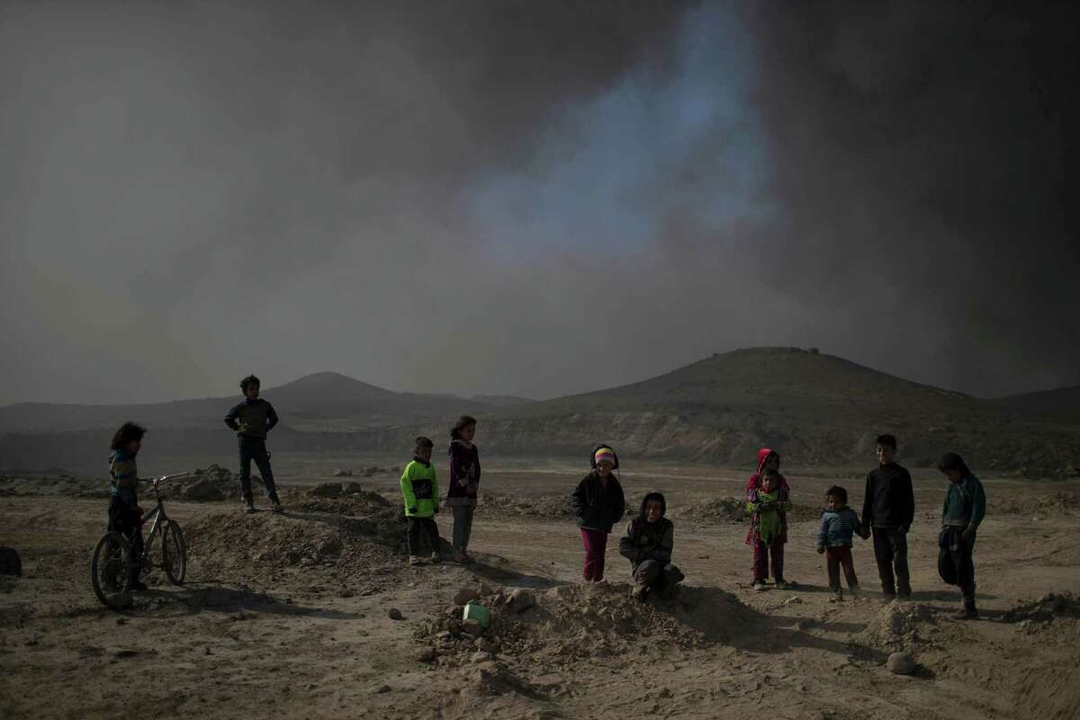 Children stand among smoke from burning oil fields in Qayara, south of Mosul, Iraq, Tuesday, Nov. 22, 2016. For months, residents of the Iraqi town of Qayara have lived in darkness from a cloud of toxic fumes released by oil fields lit by retreating Islamic State fighters. (AP Photo/Felipe Dana)