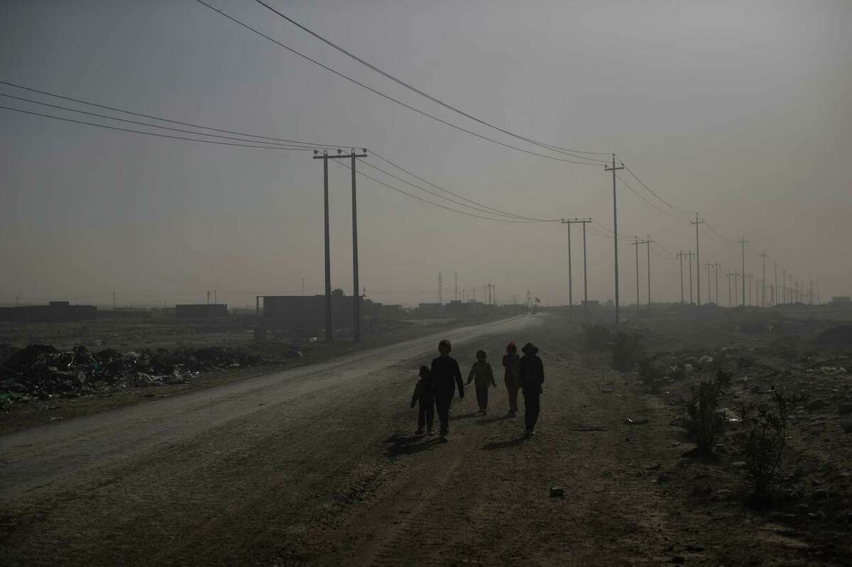 Children walk among smoke from burning oil fields in Qayara, south of Mosul, Iraq, Tuesday, Nov. 22, 2016. For months, residents of the Iraqi town of Qayara have lived in the darkness from a cloud of toxic fumes released by oil fields lit by retreating Islamic State fighters. (AP Photo/Felipe Dana)