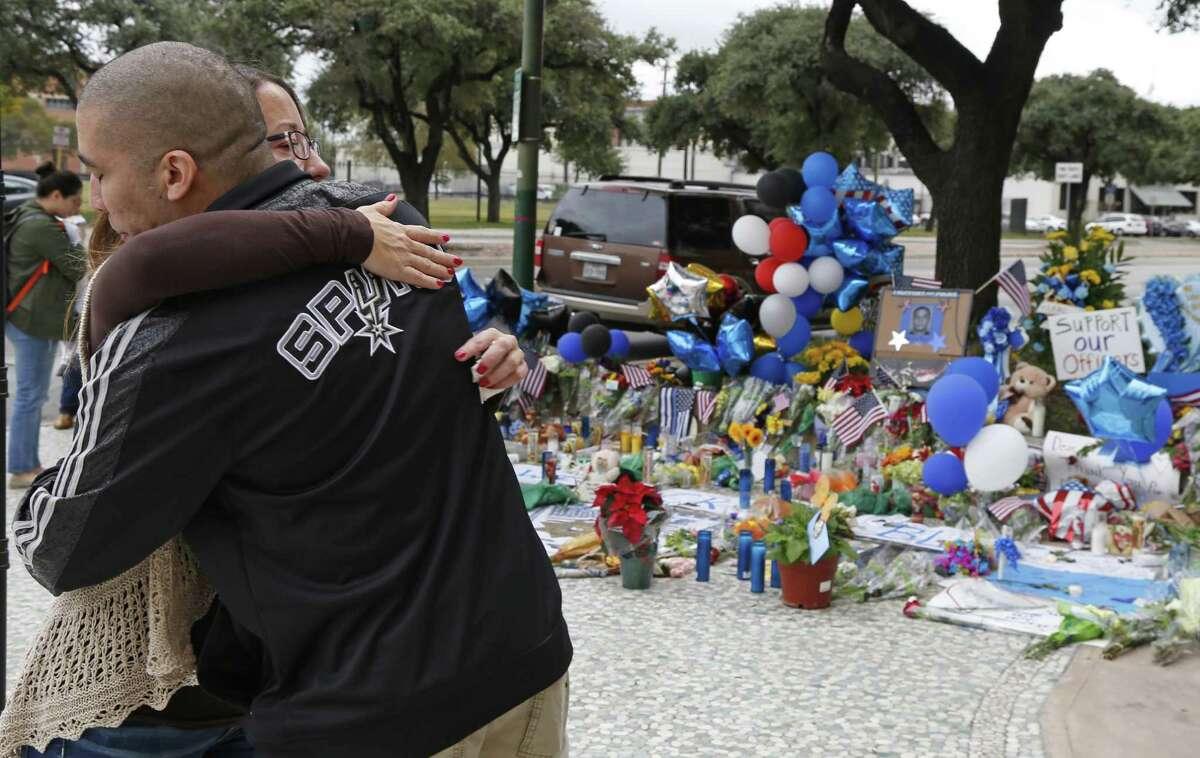 Melissa Graham hugs police officer Robert Gaitan at make-shift memorial for slain police officer Marconi at at the San Antonio Police Headquarters on Tuesday, November 22, 2016.