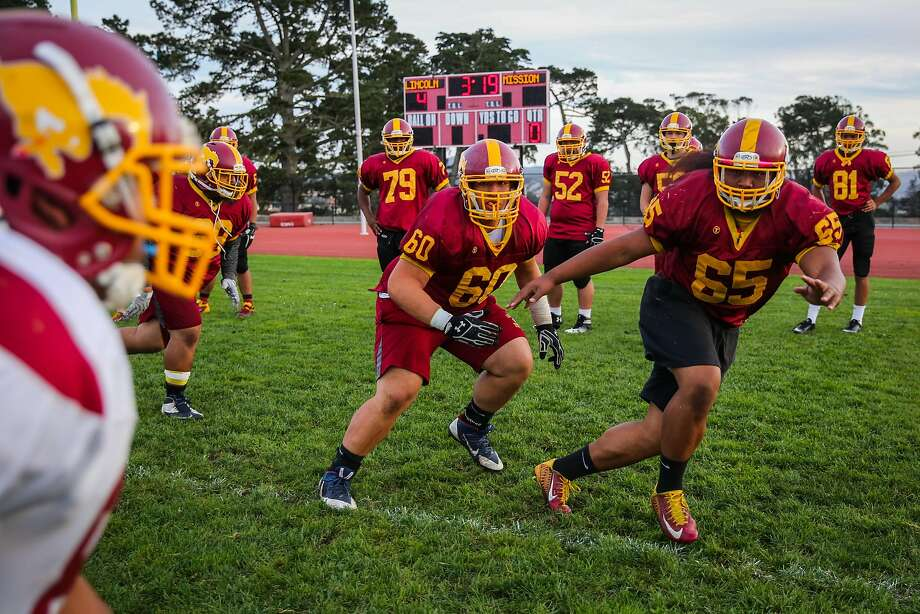 Ronald Phelps (center, No. 60) and Timoteo Potasi (No. 65) are two-way linemen who together have 240 rushing yards and six TDs for Lincoln, which plays Mission in the Turkey Day Game. Photo: Gabrielle Lurie, The Chronicle