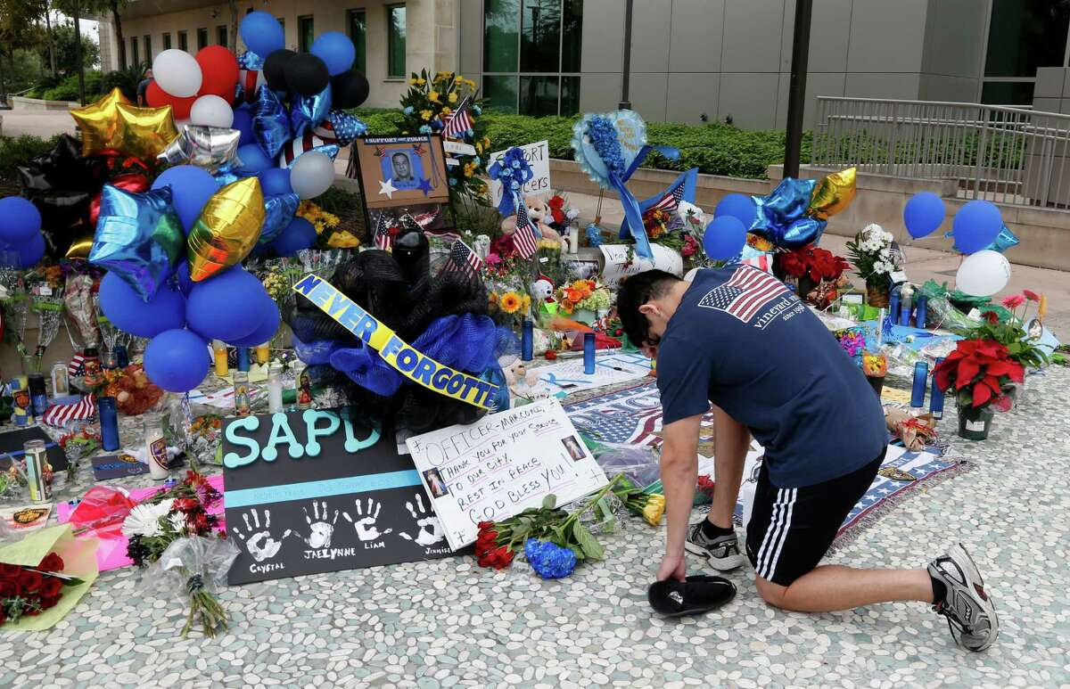 Jeffrey Saenz placed some flowers at make-shift memorial at the San Antonio Police Headquarters for slain police officer Marconi on Tuesday, November 22, 2016.