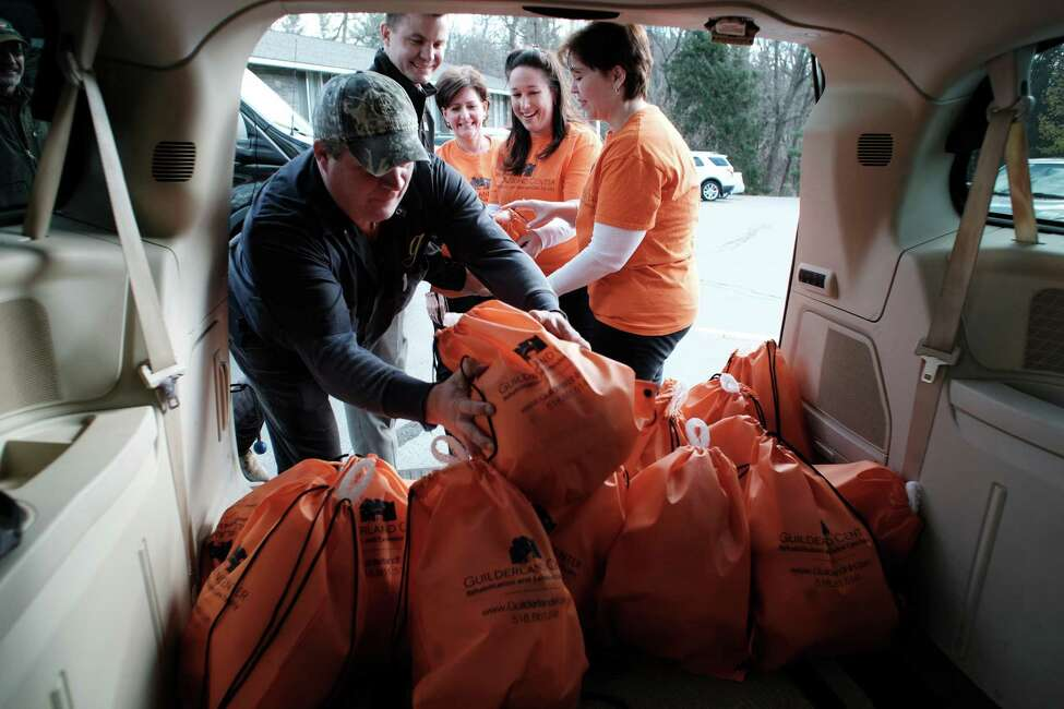 Guilderland Center Rehabilitation and Extended Care Facility employees, left to right, Brian Keller, transport driver, Gary March, assistant administrator, Erica Rogan, a hospital liaison, Jessica Barbuti, a hospital liaison, and Wendy Decker, an admissions coordinator, unload turkeys at the Guilderland Food Pantry on Tuesday, Nov. 22, 2016, in Guilderland, N.Y. This year the Guilderland Center Rehabilitation and Extended Care Facility provided half the turkeys going into the food packages. The food pantry, which was started in 1979, has been doing the Thanksgiving Holiday meals for families for over 10 years. This year they will feed 72 families, up 10 families from last year. The food bags are made up from donations from area churches, individuals and businesses. Outside of the holidays the food pantry serves roughly 289 clients in the Guilderland area. In 2015 the community donated 5,000 pounds of food, which created 12,000 meals. (Paul Buckowski / Times Union)