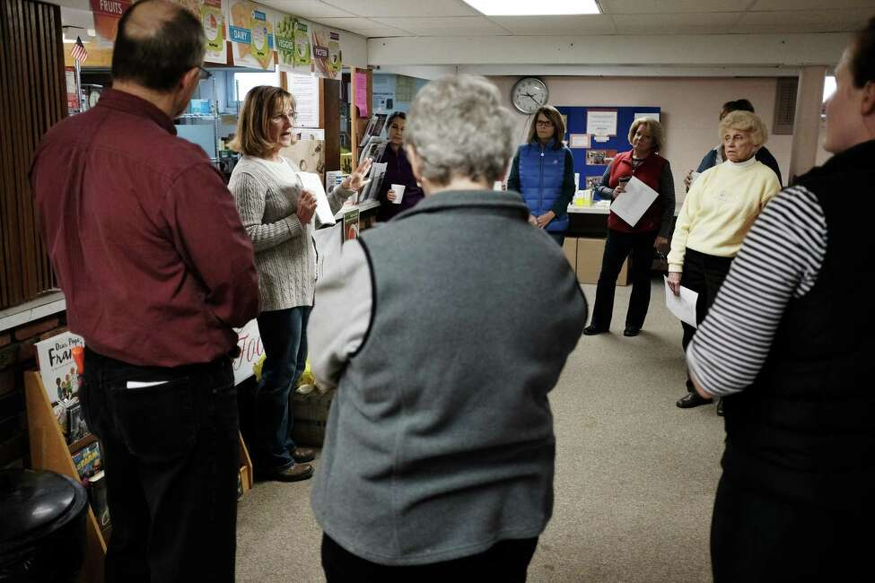 Susan Hennessy, second from left, co-director of the Guilderland Food Pantry, talks with volunteers at the pantry in the basement of the Hamilton Union Presbyterian Church, before making up food packages for families, on Tuesday, Nov. 22, 2016, in Guilderland, N.Y. The food pantry, which was started in 1979, has been doing the Thanksgiving Holiday meals for families for over 10 years. This year they will feed 72 families, up 10 families from last year. The food bags are made up from donations from area churches, individuals and businesses. This year the Guilderland Center Rehabilitation and Extended Care Facility provided half the turkeys going into the food packages. Outside of the holidays the food pantry serves roughly 289 clients in the Guilderland area. In 2015 the community donated 5,000 pounds of food, which created 12,000 meals. (Paul Buckowski / Times Union)