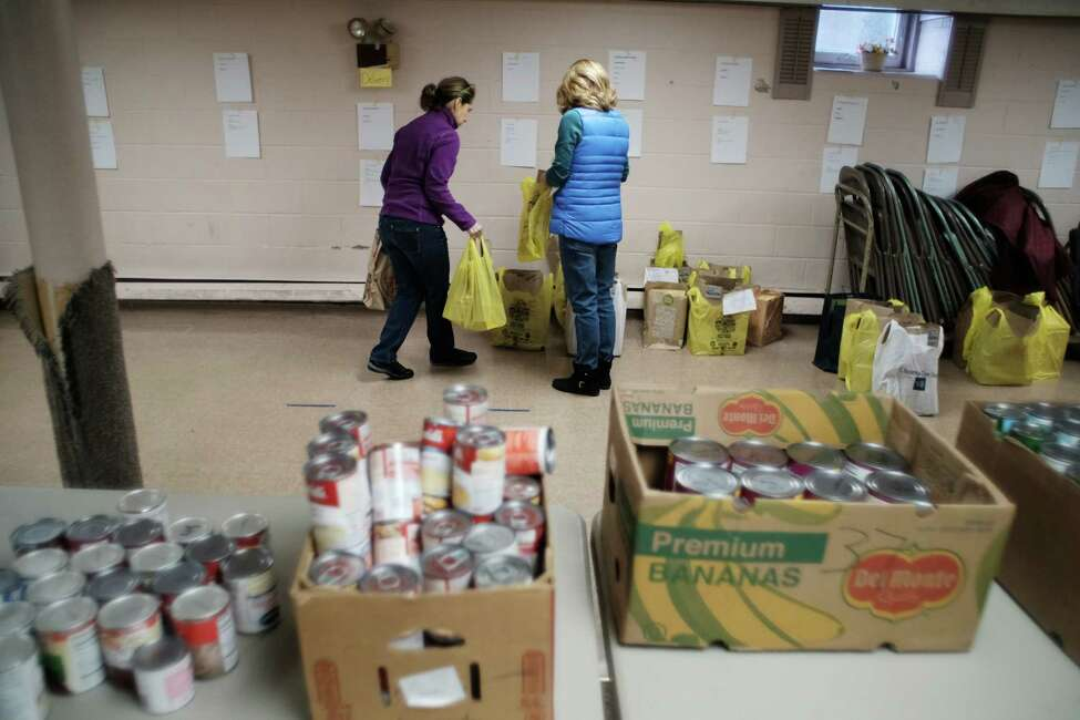 Volunteers, Judy Miller, left, of Guilderland and Ellen Gilbert of Altamont help pack up food bags for families at the Guilderland Food Pantry in the basement of the Hamilton Union Presbyterian Church, on Tuesday, Nov. 22, 2016, in Guilderland, N.Y. The food pantry, which was started in 1979, has been doing the Thanksgiving Holiday meals for families for over 10 years. This year they will feed 72 families, up 10 families from last year. The food bags are made up from donations from area churches, individuals and businesses. This year the Guilderland Center Rehabilitation and Extended Care Facility provided half the turkeys going into the food packages. Outside of the holidays the food pantry serves roughly 289 clients in the Guilderland area. In 2015 the community donated 5,000 pounds of food, which created 12,000 meals. (Paul Buckowski / Times Union)