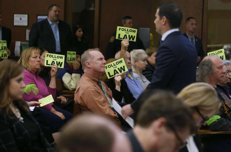 """Santa Clara residents hold """"Follow the Law"""" signs as San Francisco 49ers' Business Operations' President Al Guido heads to sit down after commenting on Niners' management of Levi's Stadium during Santa Clara City Council meeting in Santa Clara, Calif., on Tuesday, November 22, 2016. Photo: Scott Strazzante, The Chronicle"""
