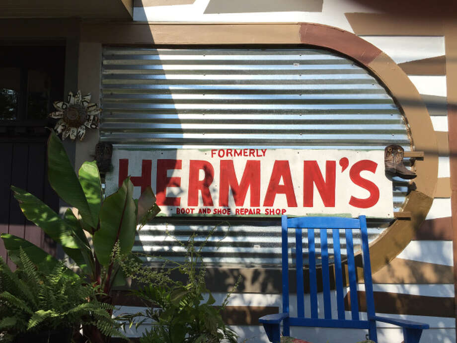 """Kevin Munsterman takes pride in living in a home that used to be  Herman's shoe repair shop. The """"Herman's"""" sign still faces the street.  He had to add """"formerly"""" to the sign because people were bringing him  their shoes. Photo: Lucas Masllorens / Modest Digs"""