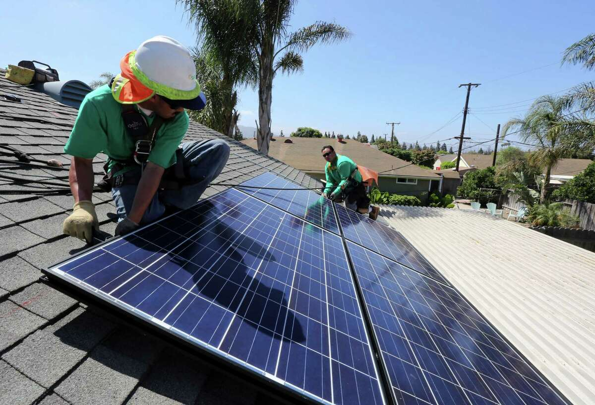 Workers from SolarCity install solar panels on the roof of a house in Camarillo, Calif.