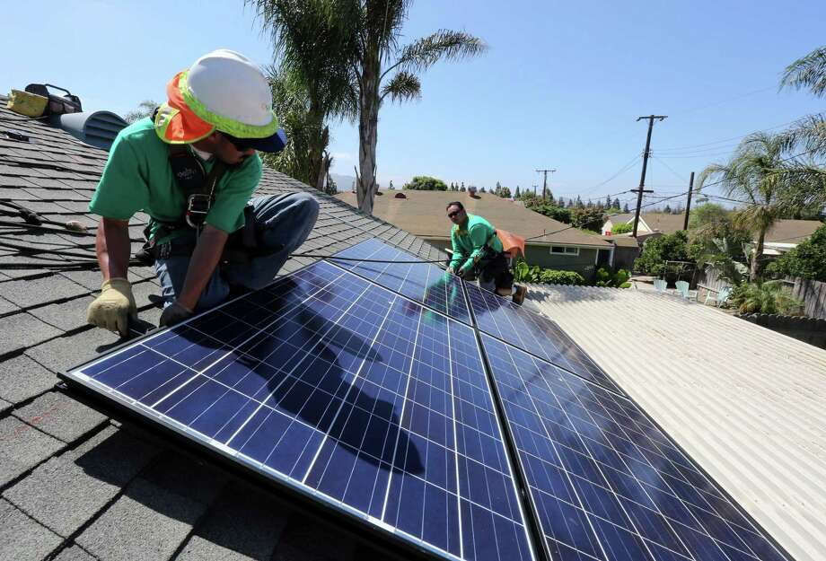Workers from SolarCity install solar panels on the roof of a house in Camarillo, Calif. Photo: J. EMILIO FLORES, STR / NYTNS