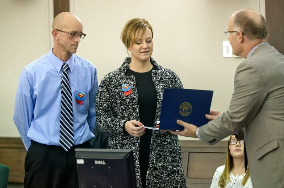 Congressman John Moolenaar, right, presents Chad and Theresa Walters the Angels in Adoption award during Michigan Adoption Day on Monday at the Midland County Courthouse. The Walters adopted Elayna, seen sitting, and her biological brother Tannar. Photo: Nick King/Midland  Daily News/Nick King