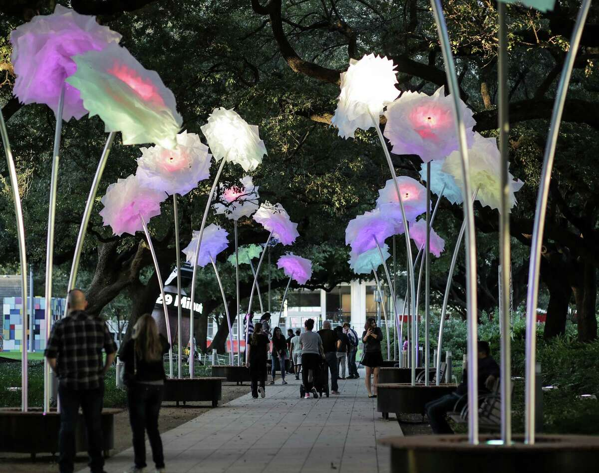 """Pedestrians walk through """"Enchanted Promenade"""" by the French art and design collective TILT at Discovery Green on Monday, Nov. 21, 2016, in Houston. ( Elizabeth Conley / Houston Chronicle )"""