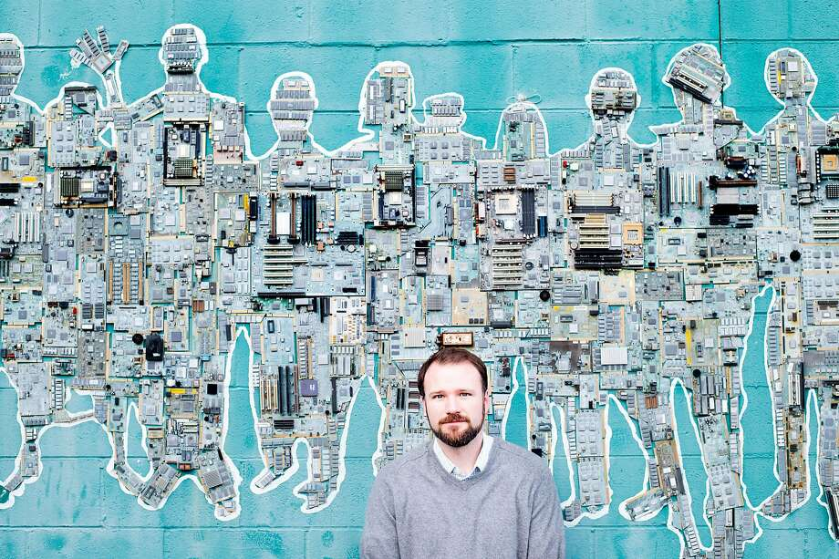 Seth Hubbert, executive director of the Oakland Technology Exchange, stands with a wall sculpture outside his nonprofit. Photo: Noah Berger, Special To The Chronicle