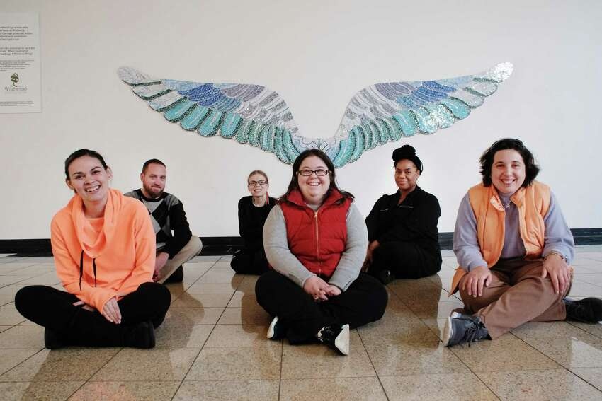 Wildwood individuals and staff members, from left to right, Katie Garcia, Matt Whelan, manager of the Without Walls Program, Marie Hutchinson, Rebecca Burliuk, Tekeah Harris, direct support professional, and Karen Gillis, pose in front of the wings covered in stained glass inside Crossgates Mall on Wednesday, Nov. 23, 2016, in Guilderland, N.Y. Artist Tamara DeMartino worked with 28 individuals and staff members of Wildwood to create the wings. (Paul Buckowski / Times Union)