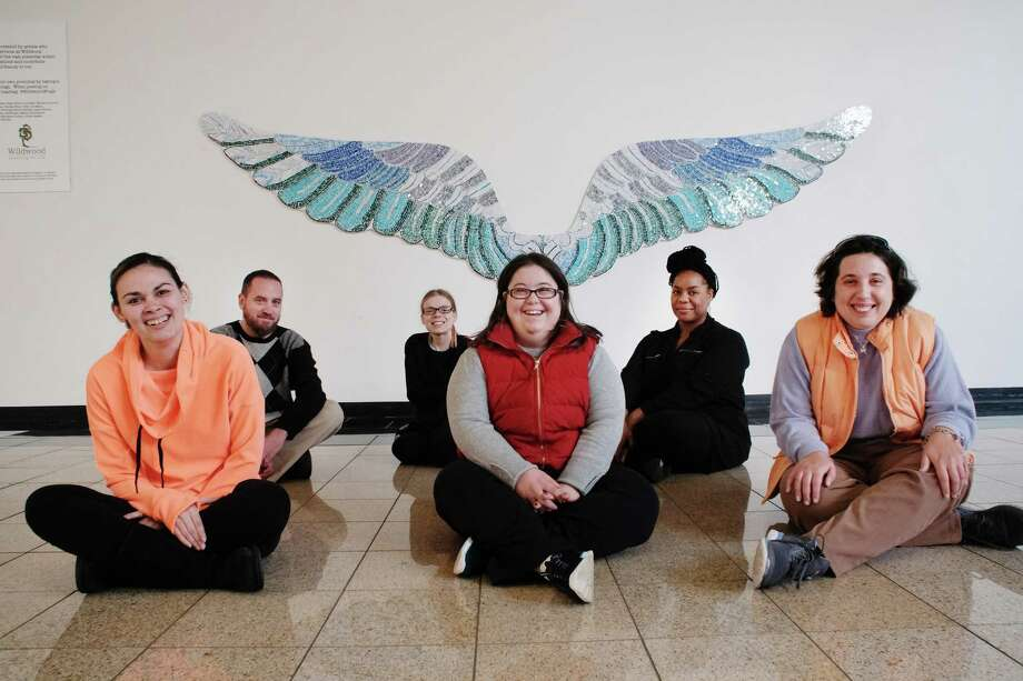 Wildwood individuals and staff members, from left to right, Katie Garcia, Matt Whelan, manager of the Without Walls Program, Marie Hutchinson, Rebecca Burliuk, Tekeah Harris, direct support professional, and Karen Gillis, pose in front of the wings covered in stained glass  inside Crossgates Mall on Wednesday, Nov. 23, 2016, in Guilderland, N.Y.  Artist Tamara DeMartino worked with 28 individuals and staff members of Wildwood to create the wings.    (Paul Buckowski / Times Union) Photo: PAUL BUCKOWSKI / 20038908A