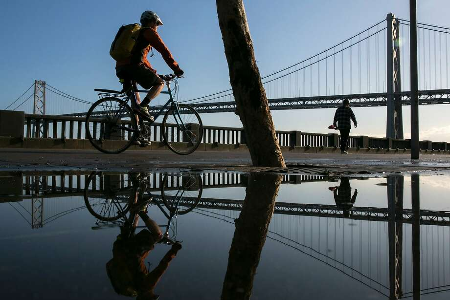 Pedestrians walk and bike past puddles along The Embarcadero that formed during overnight showers, on Wednesday, Nov. 23, 2016 in San Francisco. The Bay Bridge is seen in the background. Photo: Santiago Mejia, The Chronicle