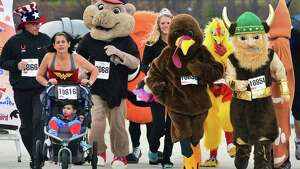 Costumed runners and regional mascots in a mini road race to promote the introduction of a costume contest in the 5K of the Troy Turkey Trot during a news conference in Riverfront Park Friday Nov. 8, 2013, in Troy, NY.  (John Carl D'Annibale / Times Union)