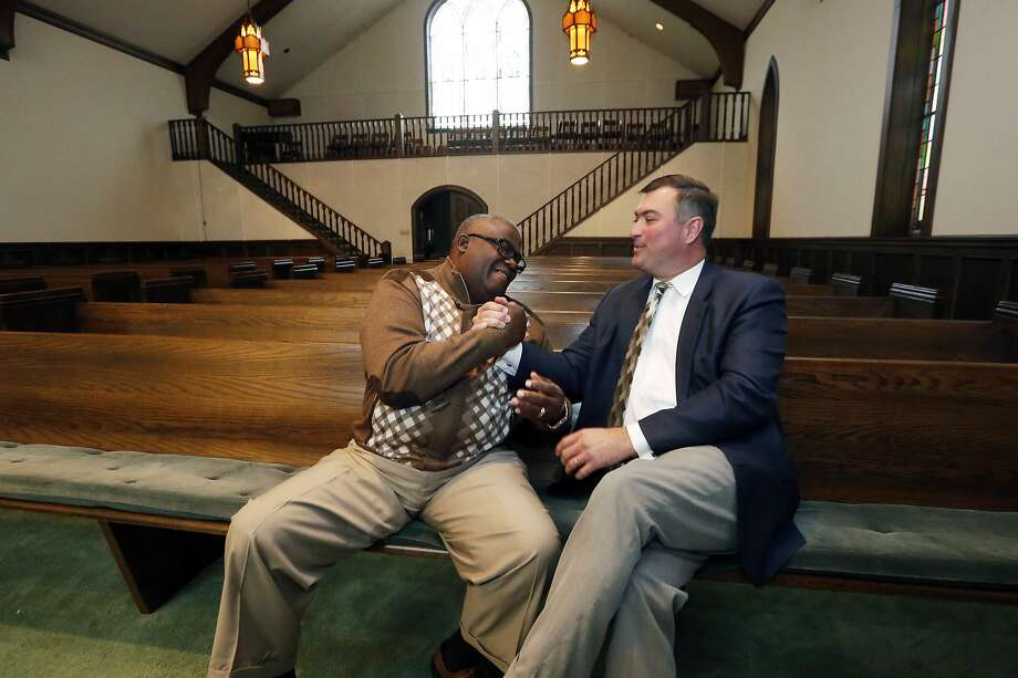 Bishop Clarence Greene (left) join hands with Pastor James Nichols at Greenville's First Baptist Church. Photo: Rogelio V. Solis, Associated Press