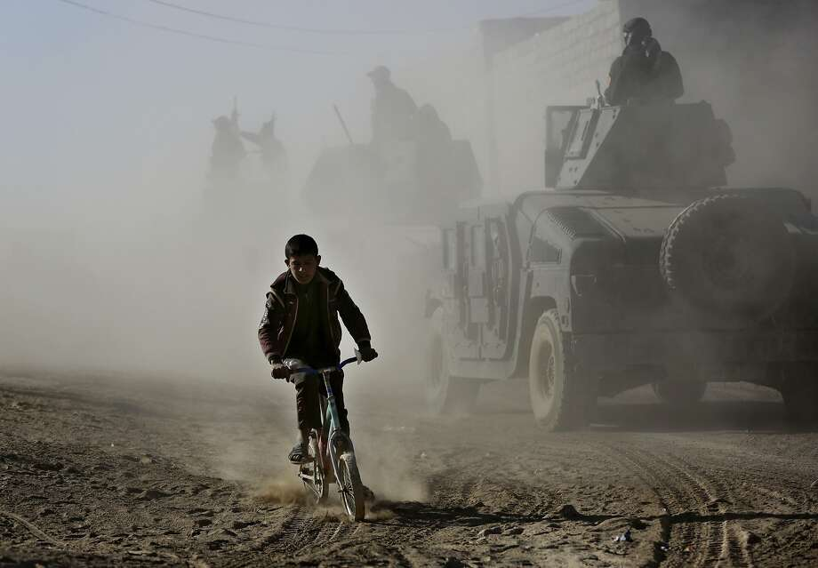 An Iraqi boy rides his bicycle as he follows special forces humvees on their way to the front line to battle Islamic State militants, in the Al-Samah neighborhood of the northern city of Mosul. Photo: Hussein Malla, Associated Press