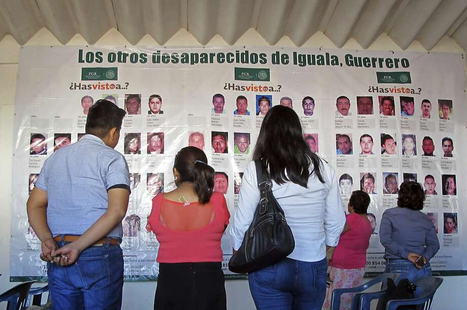 New arrivals look at photographs of the missing at the site of the future headquarters for families searching for relatives in Iguala, Mexico. Photo: Chris Sherman, Associated Press