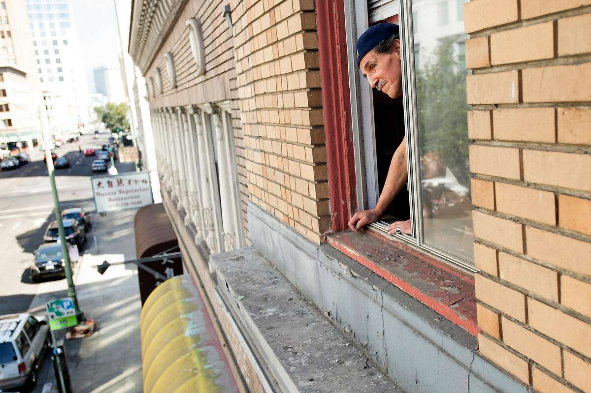 Orlando Chavez looks out from his room at the Travelers Hotel in Oakland, Calif., on Monday, Oct. 10, 2016. The century-old SRO (single-room-occupancy) hotel is being converted into market-rate housing for young professionals leaving current tenants with an uncertain future.