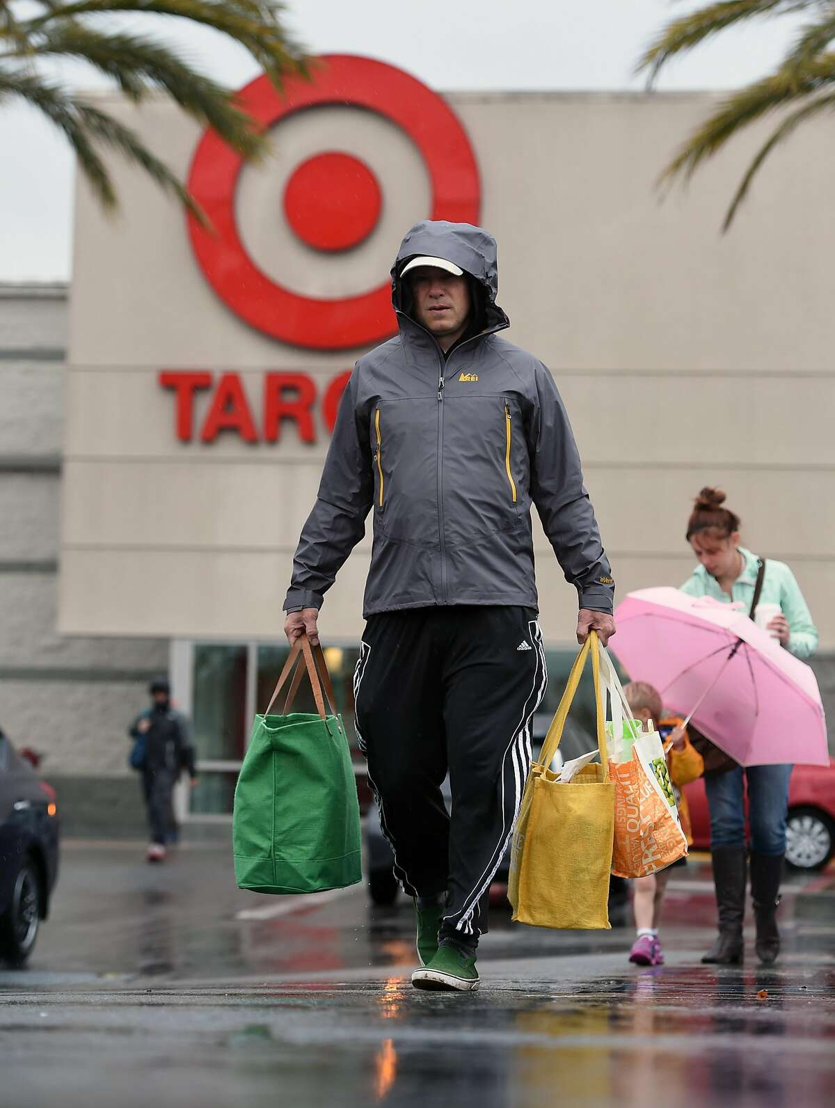 Shoppers walk in the rain outside a Target store in Emeryville, Calif. on November 19, 2016.