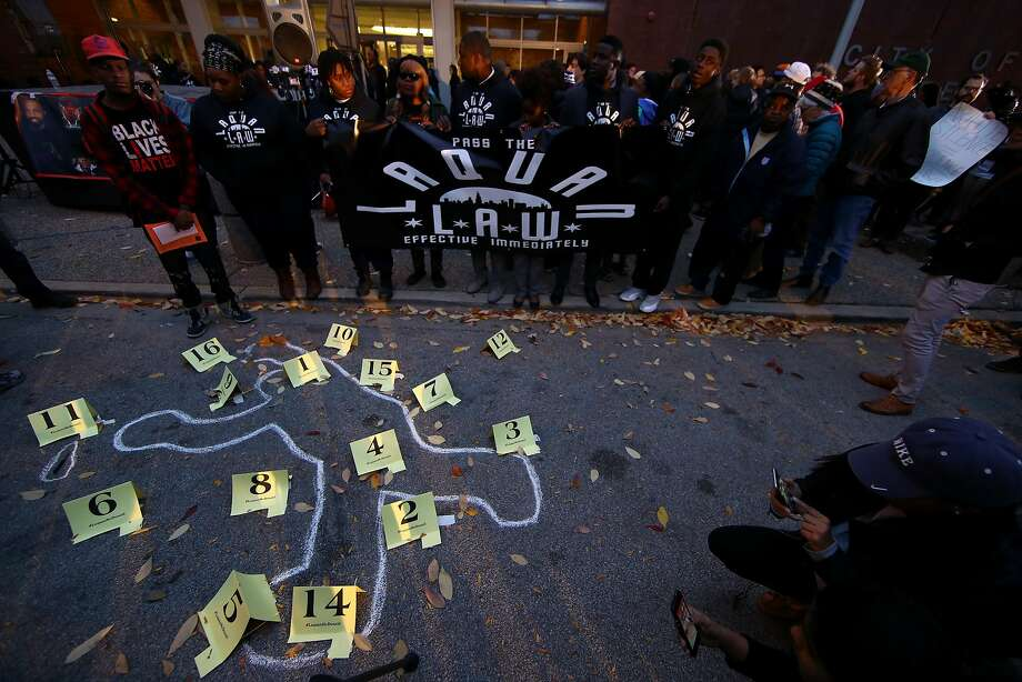 People stand in silent homage last month in front of the chalk outline drawn by supporters where Laquan McDonald was shot and killed by police officers two years ago. Photo: Anadolu Agency, Getty Images