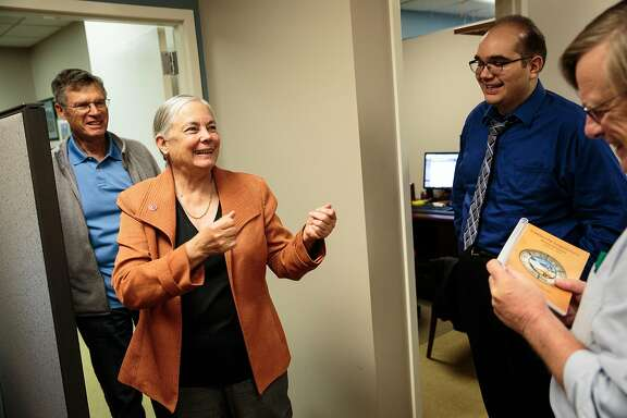 California State Senator Fran Pavley, D-Agoura Hills, center, jokes with aide Chris Chavez, right, as her husband Andy Pavley, left, looks on in her office at the State Capitol in Sacramento, California, November 2, 2016.