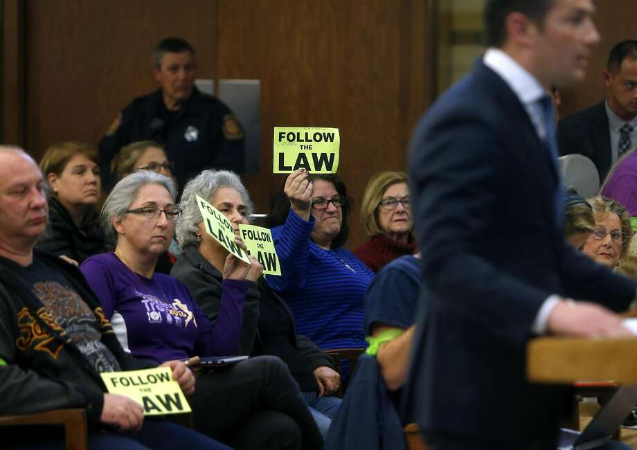 "Santa Clara residents hold ""Follow the Law"" signs as 49ers executive Al Guido speaks about management of Levi's Stadium at the City Council meeting Tuesday. Photo: Scott Strazzante, The Chronicle"