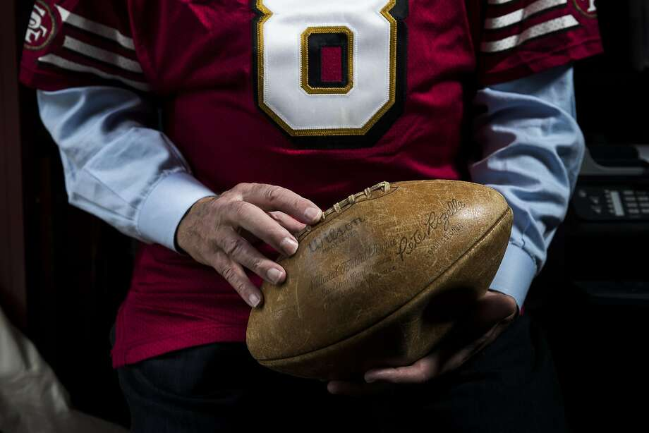 Dr. Tom Addison holds a game ball souvenir from Super Bowl I. He recently lost $12,000 reselling 49ers seat licenses. Photo: Stephen Lam, Special To The Chronicle