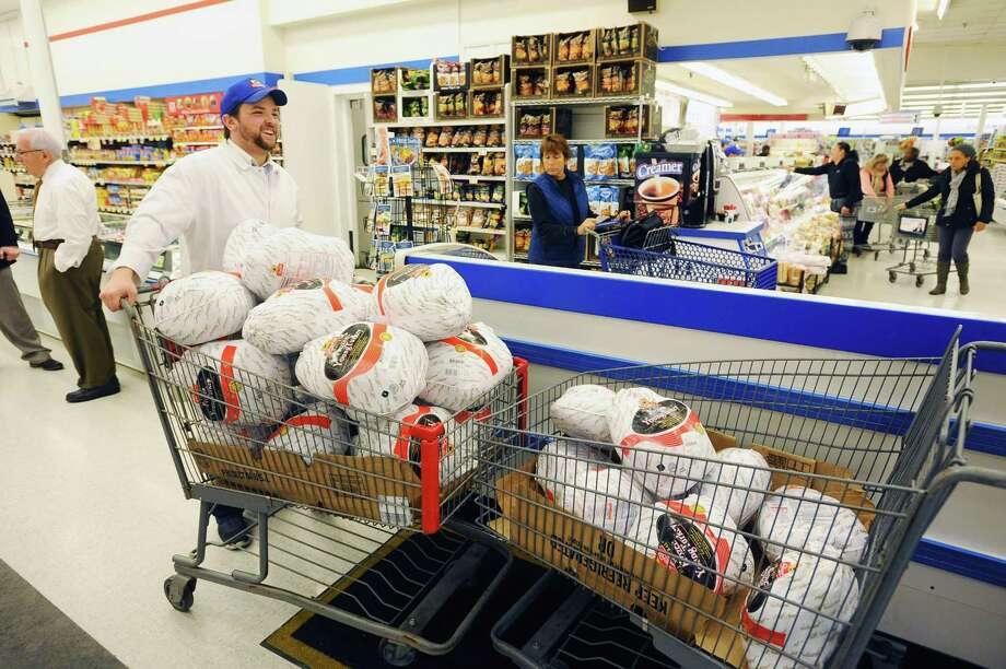 Employee John Tully restocks turkeys inside ShopRite on Shippan Avenue in Stamford on Tuesday. Photo: Michael Cummo / Hearst Connecticut Media / Stamford Advocate