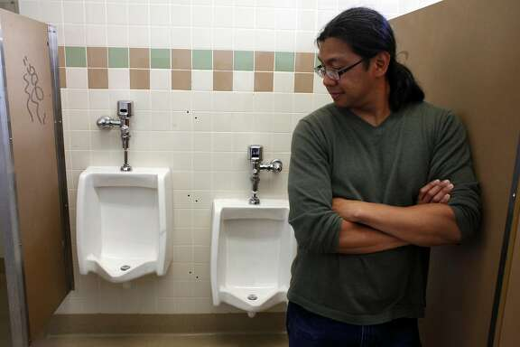 Teacher Conrad Benedicto stands next to the low flush urinal, Friday September 20, 2013, at Balboa High School in San Francisco, Calif. Benedicto worked with students from last year who were concerned with the amount of energy and water that the standard urinals used and worked to upgrade the boys restrooms.