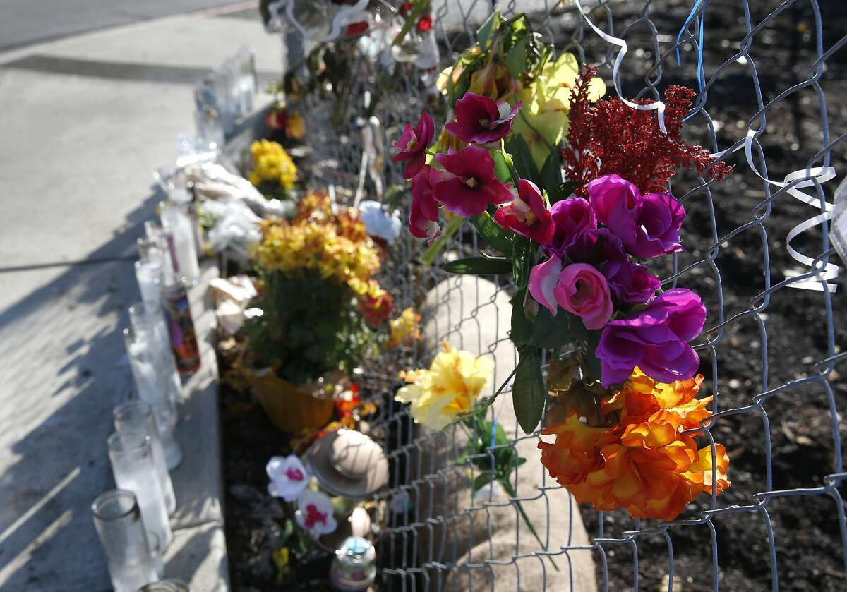 A memorial of flowers and candles are arranged at Appian Way and Garden Road in El Sobrante, Calif. on Wednesday, Nov. 23, 2016 near the spot where William Sims was slain earlier this month. One man is in custody and two others are being sought for the murder of Sims, 28, which police has labeled as a hate crime.